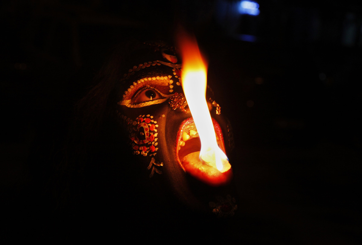 In this, Sunday, Oct. 21, 2012, photo, an Indian performer disguised as Hindu Goddess Kali performs with fire during Navratri