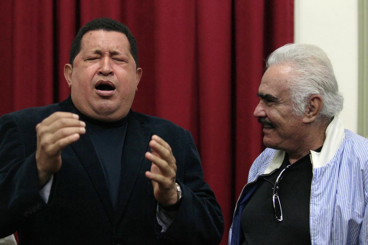 Venezuela's President Hugo Chavez, left, sings a Mexican ranchera song next to Mexican singer Vicente Fernandez in Caracas, V