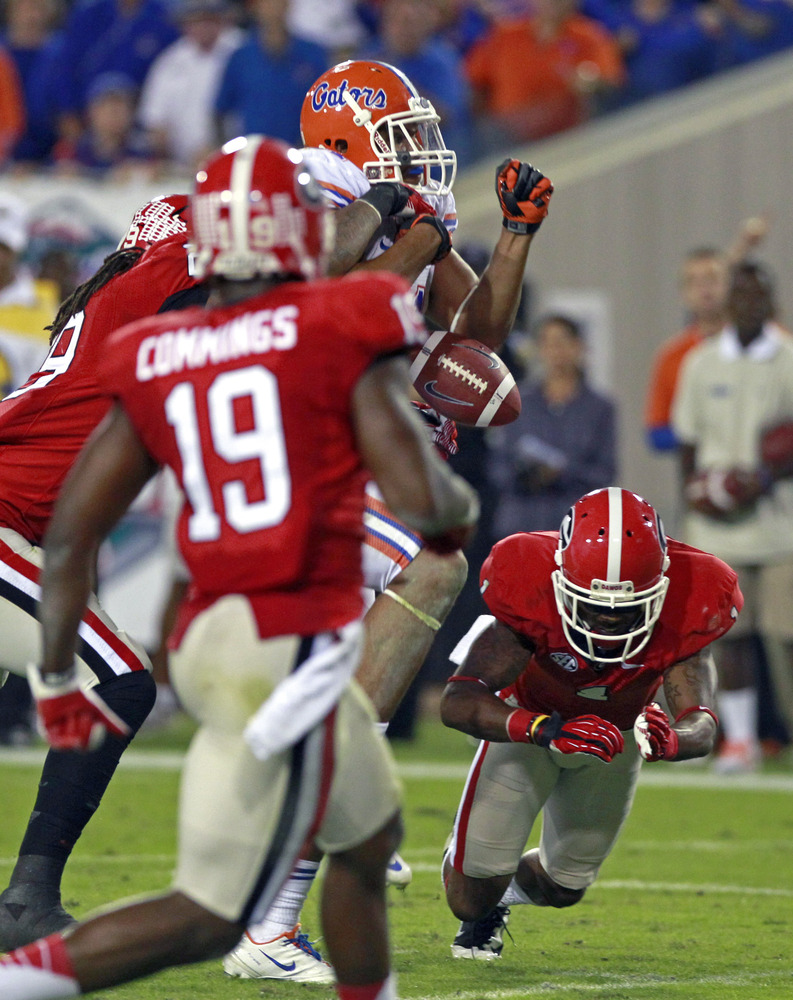 Florida tight end Jordan Reed, center, fumbles the ball as he is hit Georgia linebacker Jarvis Jones, left, during the second