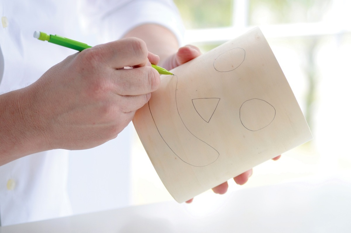 Use a pencil to sketch the eyes, nose, and mouth onto the craft bucket. Instead of a craft bucket, you could also use an empt