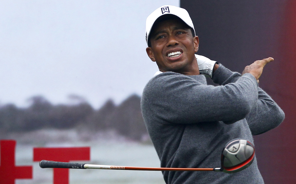 Tiger Woods lets go of his club after his tee shot on the first hole during his 18-hole medal-match against Rory McIlroy at t