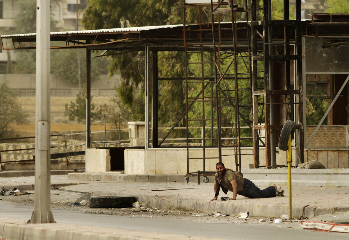 A Syrian man who was shot by a sniper waits to be rescued by members of the Al-Baraa Bin Malek Batallion, part of the Free Sy