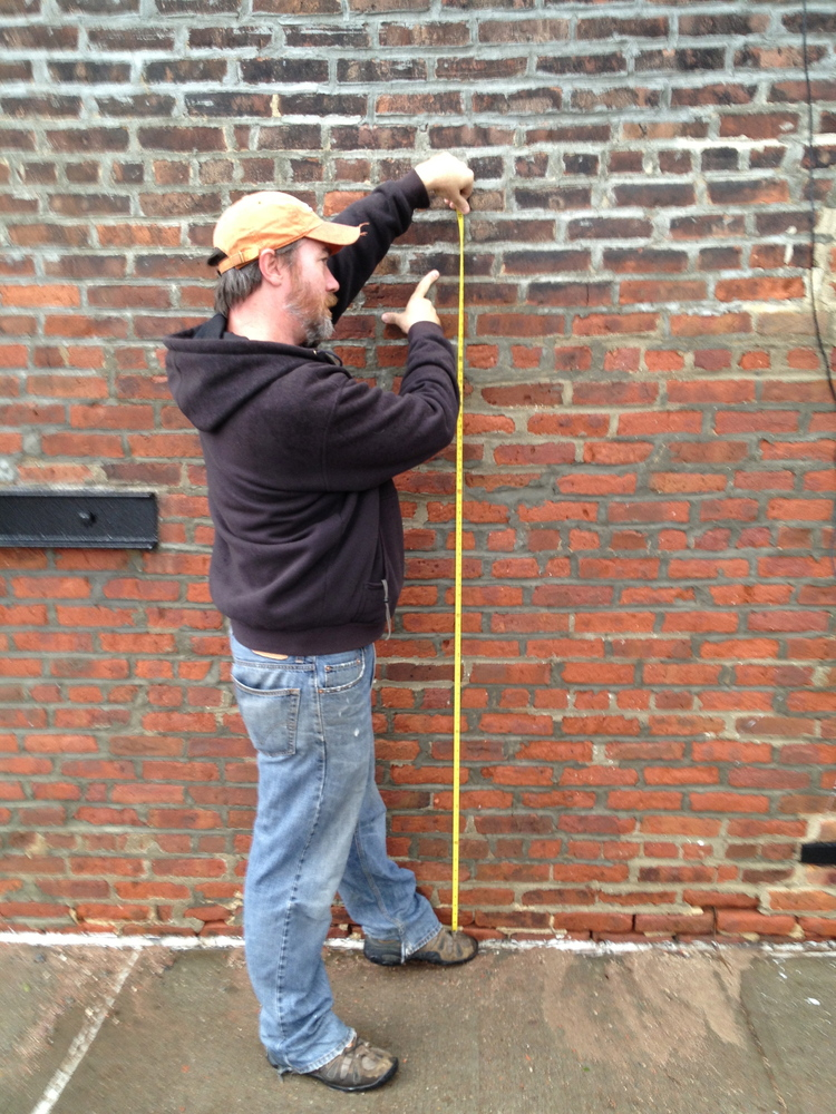 Ethan Fugate, 41, shows the high water mark on a building in Red Hook, Brooklyn.