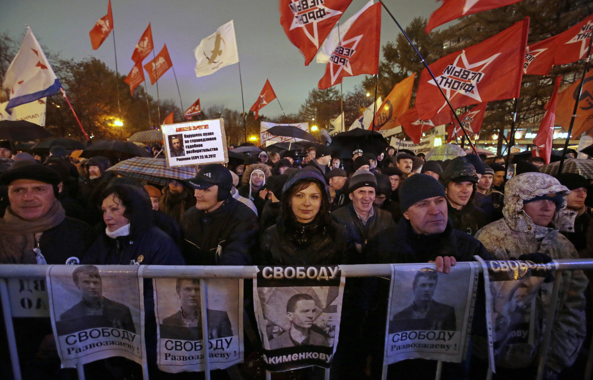 Demonstrators hold posters with portraits of jailed opposition activists Vladimir Akimenkov and Leonid Razvozzhayev and deman