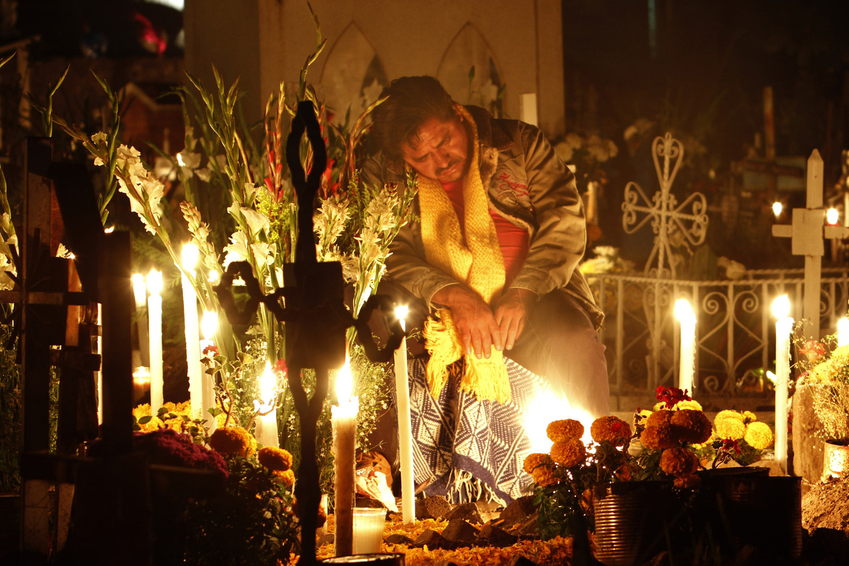 A man rests at the grave site of a departed loved one at the San Gregorio cemetery during the Dia de los Muertos or Day of th