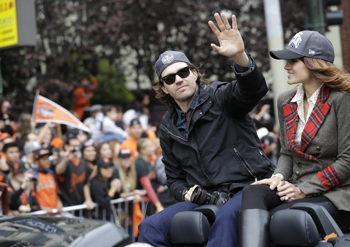 San Francisco Giants pitcher Barry Zito waves while sitting next to his wife, Amber Seyer, during the baseball team's World S