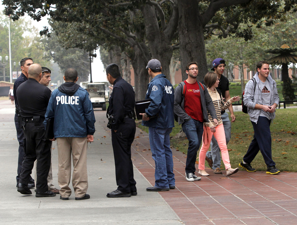 University students walk to classes as Los Angeles police officers investigate a shooting that occurred Wed. night at a hallo