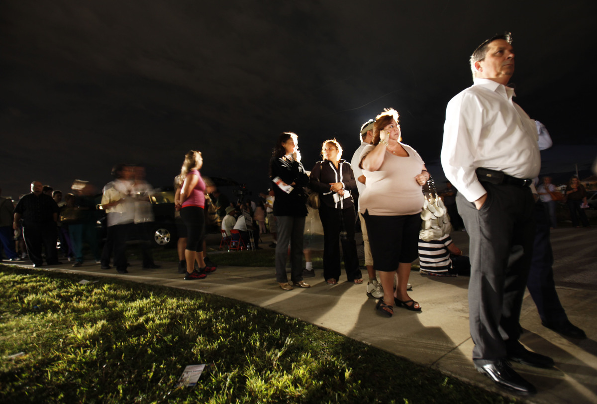 Voters line up in the dark to cast their ballots at a polling station, Tuesday, Nov. 6, 2012 in Miami. After a grinding presi