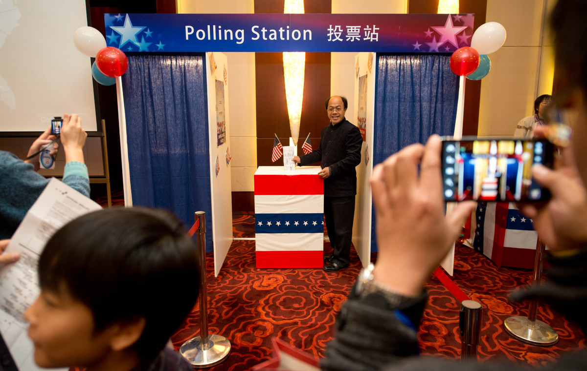 People try out a mock polling station at a hotel during a US presidential election results event organised by the US embassy
