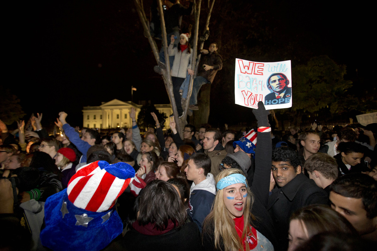 """Kelly Rodgers, 18, of Philadelphia, holds a sign saying """"We Will Barack You"""" as people celebrate outside of the White House a"""