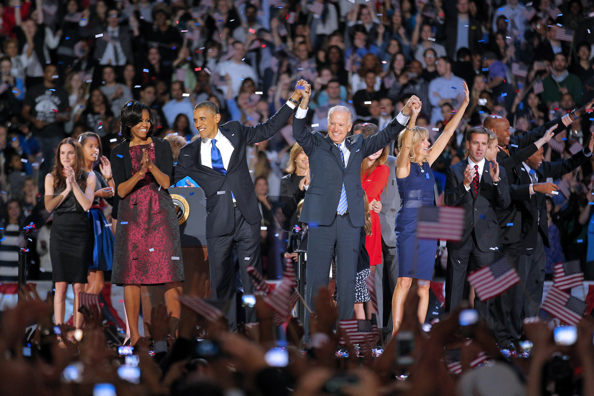 President Barack Obama and wife Michelle hold hands with Vice President Joe Biden and his wife Jill following Obama's victory