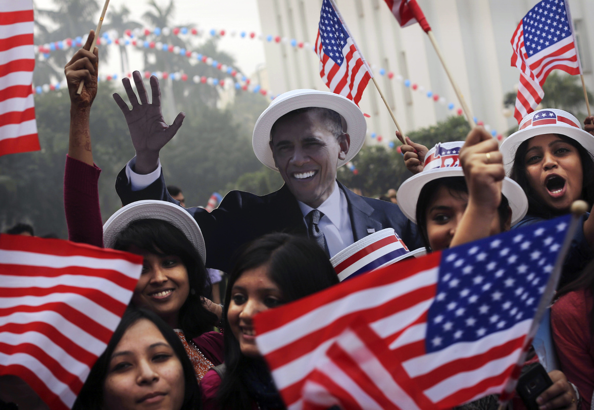 Indian students react in front of photographers next to a cardboard cutout in the likeness of U.S. President Barack Obama aft
