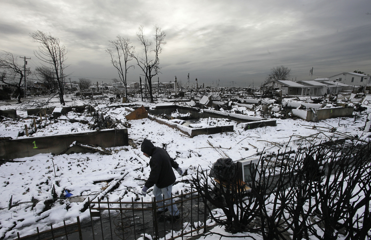 Damon Rasinya carts debris from his family home past the fire-scorched landscape of Breezy Point after a Nor'easter snow, Thu