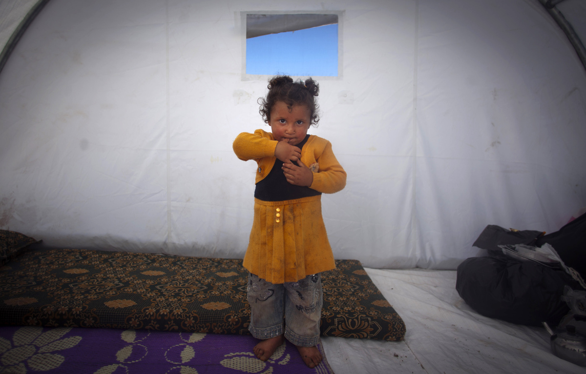 In this Wednesday, Nov. 7, 2012 photo, Fatma Zatar, 2, who fled with her family from the violence in their village poses for