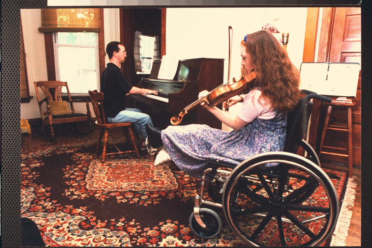 Wheelchair-bound 20-yr-old prodigy violinist Rachel Barton playing violin as pianist Patrick Sinozich plays along w. her in l