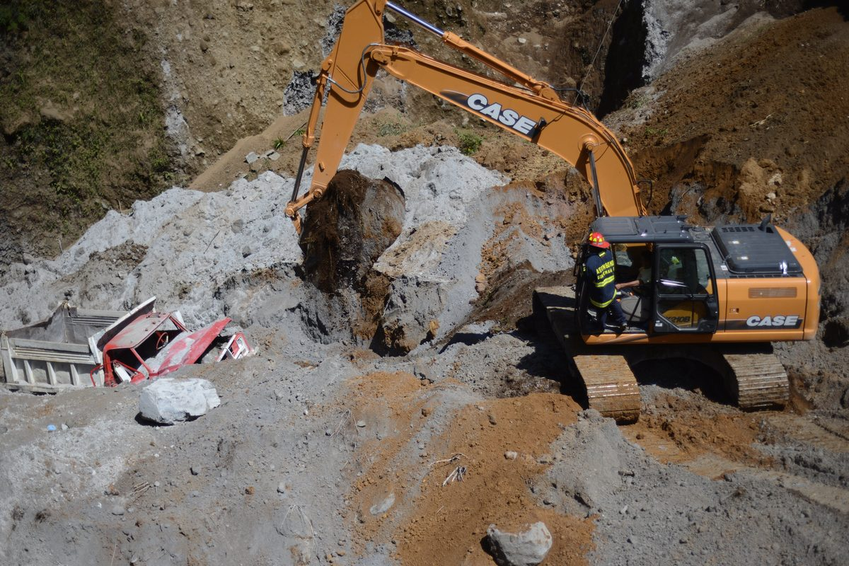 Firefighters with heavy equipment excavate searching people feared buried at a sand mine by an earthquake on the eve, in San