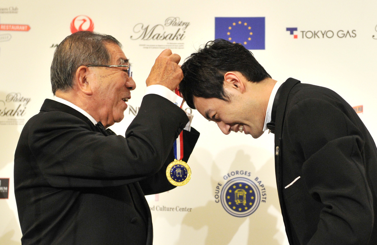 Shin Miyazaki of Japan is given a medal by Hisanori Isomura, president of committee for the competition as he celebrates his