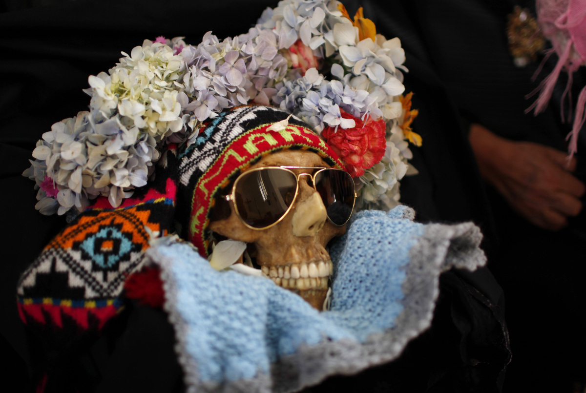 A decorated human skull or Natita is carried out of the Cementerio General's chapel and to the Natitas Festival at the larges