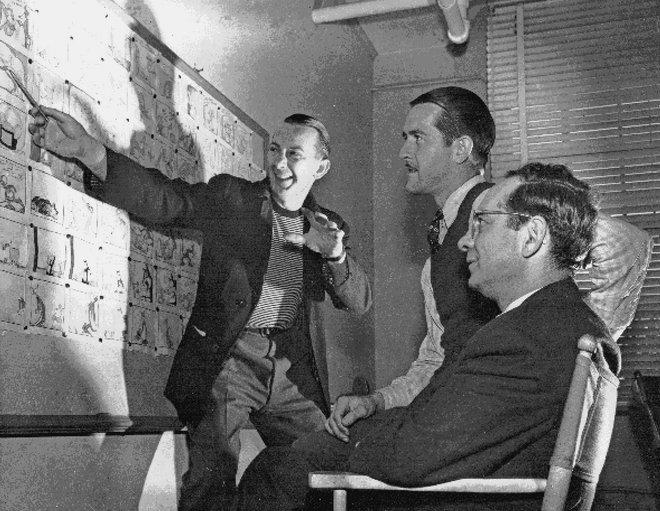 Warren Foster (standing) takes Bob McKimson and Eddie Selzer through a storyboard.