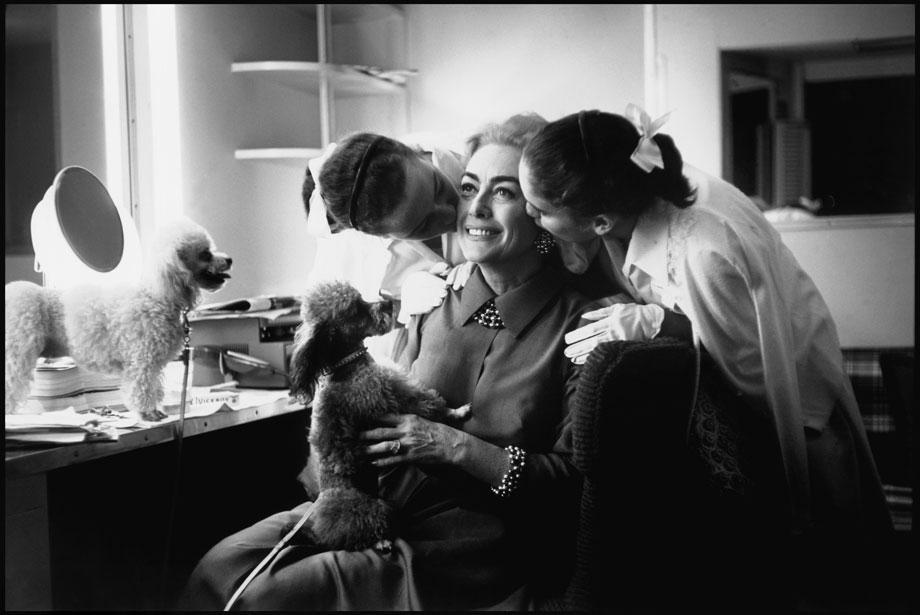 Joan Crawford with her twin daughters, Kathy and Cindy, and her poodles in Hollywood, 1959.