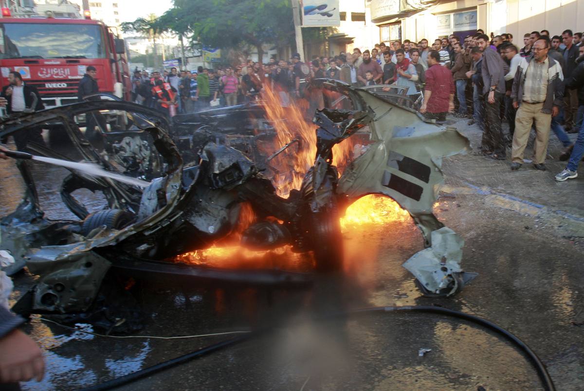 People look at a wreckage of the car in which was killed Ahmed Jabari, head of the Hamas military wing in Gaza City, Wednesda