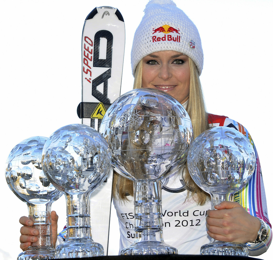 This March 18, 2012 file photo shows Lindsey Vonn, of the United States, posing with her alpine ski, women's World Cup trophi