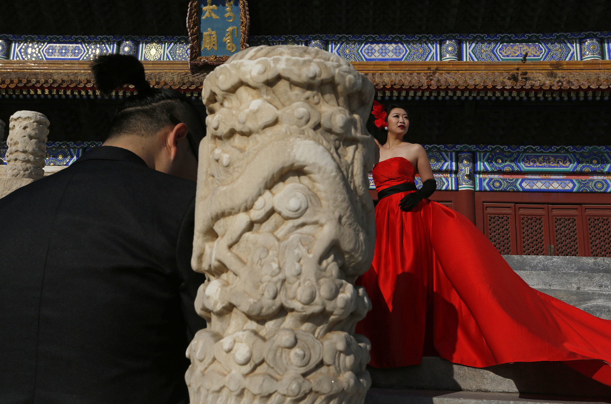 In this Nov. 12, 2012 photo, a Chinese bride wearing a red gown poses for photos in front of the Imperial Ancestral Temple in