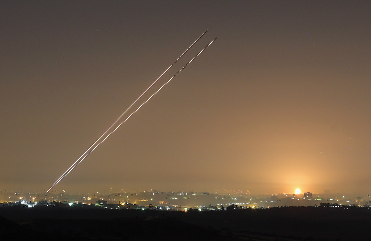 During the last hour of hostilities, militants launch rockets from Gaza City as an Israeli bomb explodes on the horizon on No