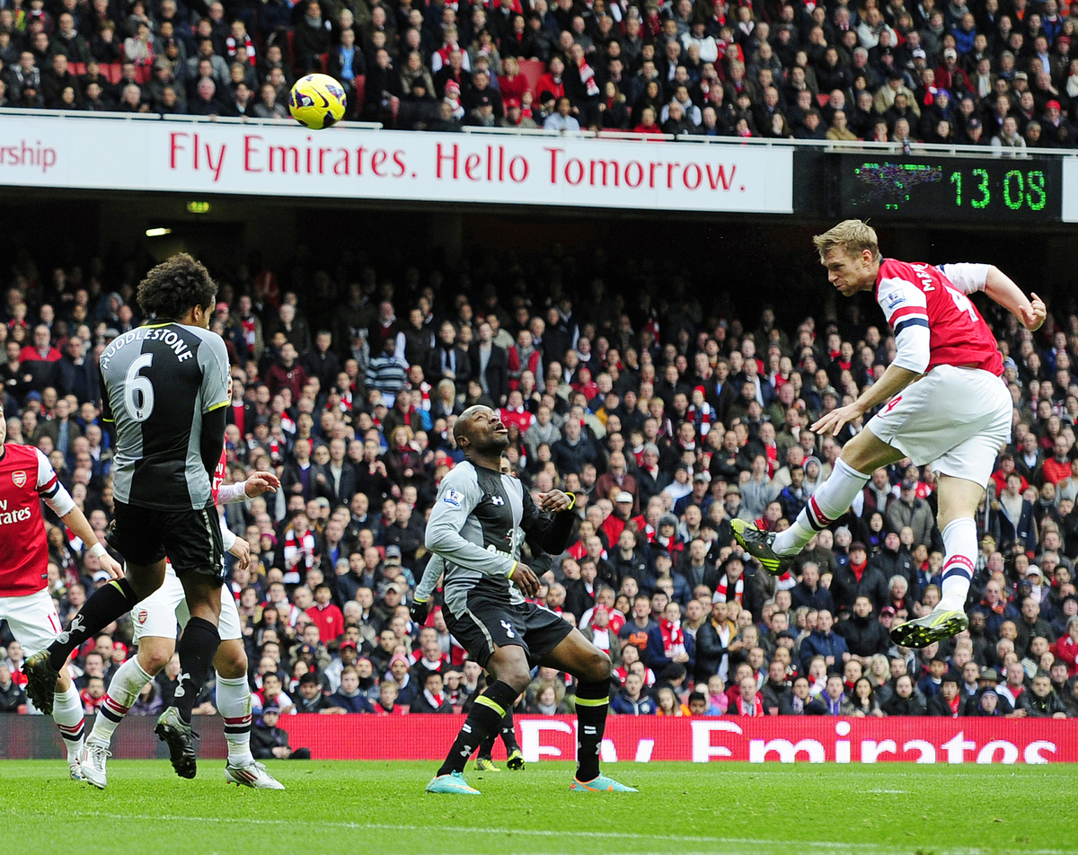 Arsenal's German defender Per Mertesacker (R) scores their first goal during the English Premier League football match betwee