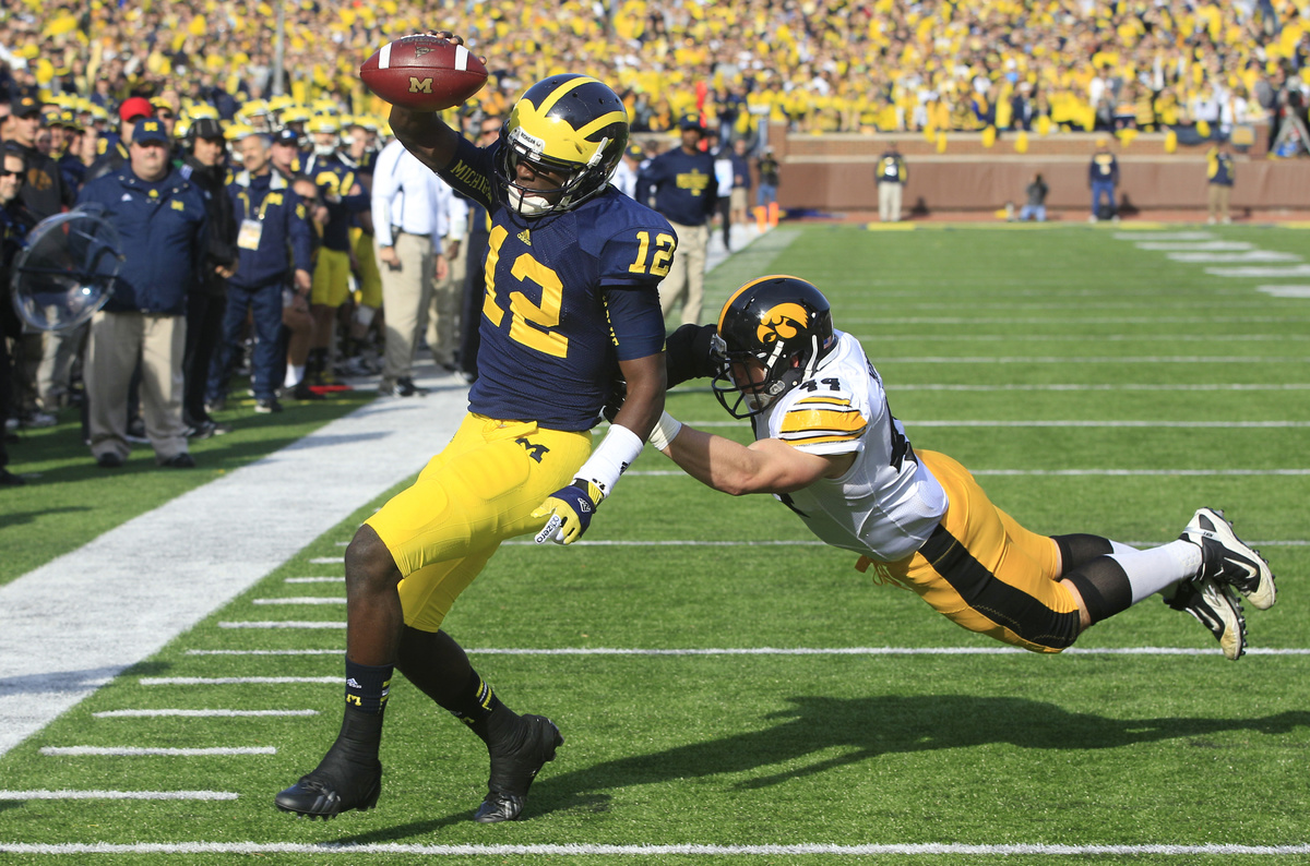 Michigan quarterback Devin Gardner (12) pulls away from Iowa linebacker James Morris (44) for a touchdown during the second q