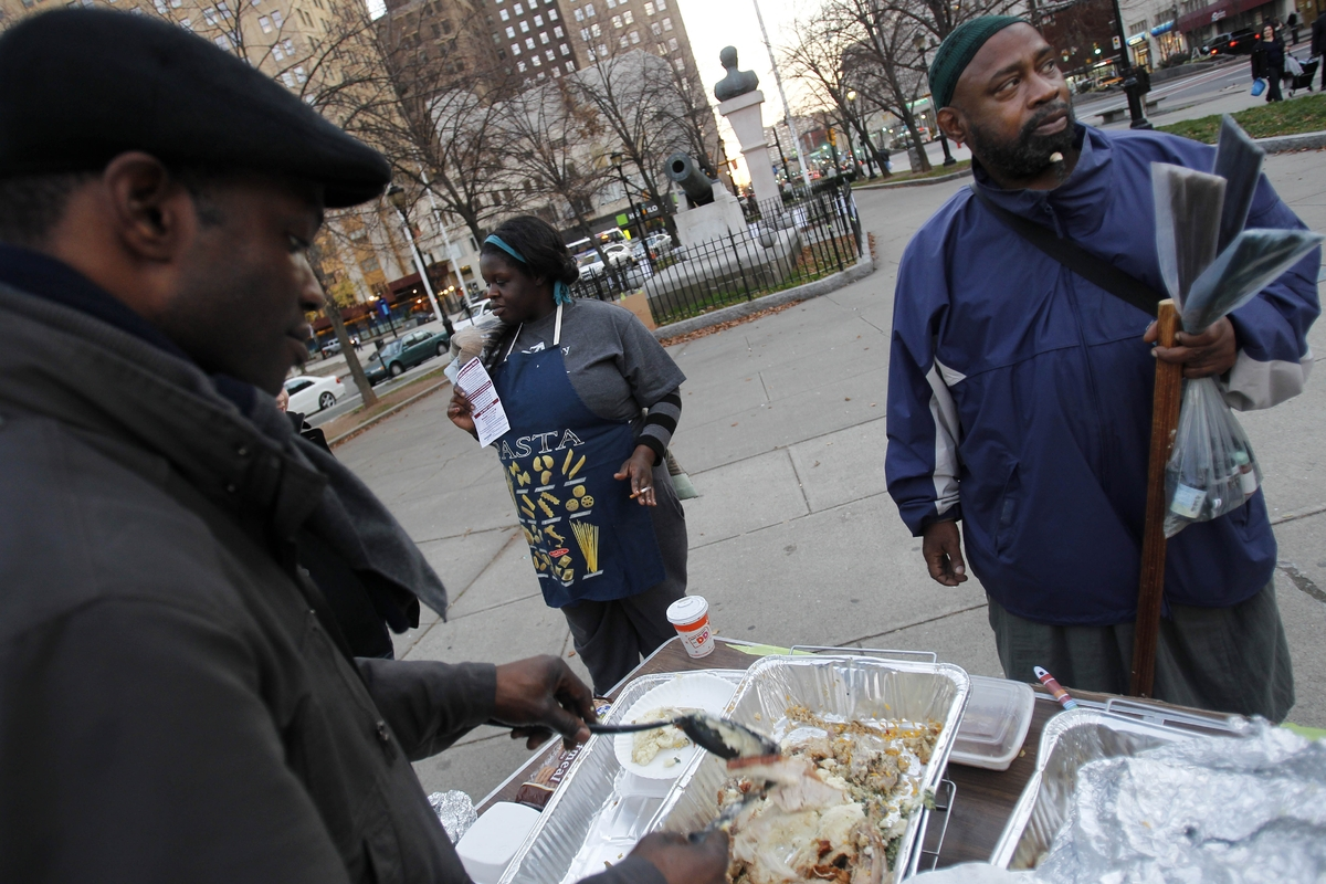Occupy Newark volunteer Chuck Nwosu, left, serves a Thanksgiving meal to Nashid Ahmad during a giveaway of hot meals at Milit