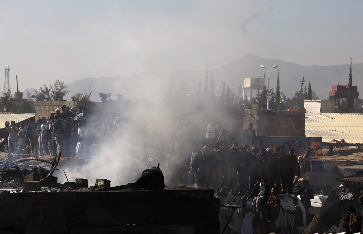 Yemeni people gather at the site of a plane crash in Sanaa, Yemen, Wednesday, Nov. 21, 2012. Yemeni security officials say a