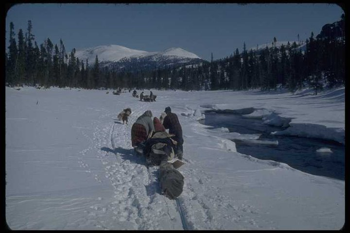 An Innu man and woman push a toboggan laden with belongings along a frozen waterway in north-eastern Canada.  The photograph