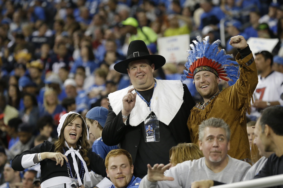 Football fans dressed as pilgrims and an Indian cheer during the second quarter of an NFL football game between the Detroit L