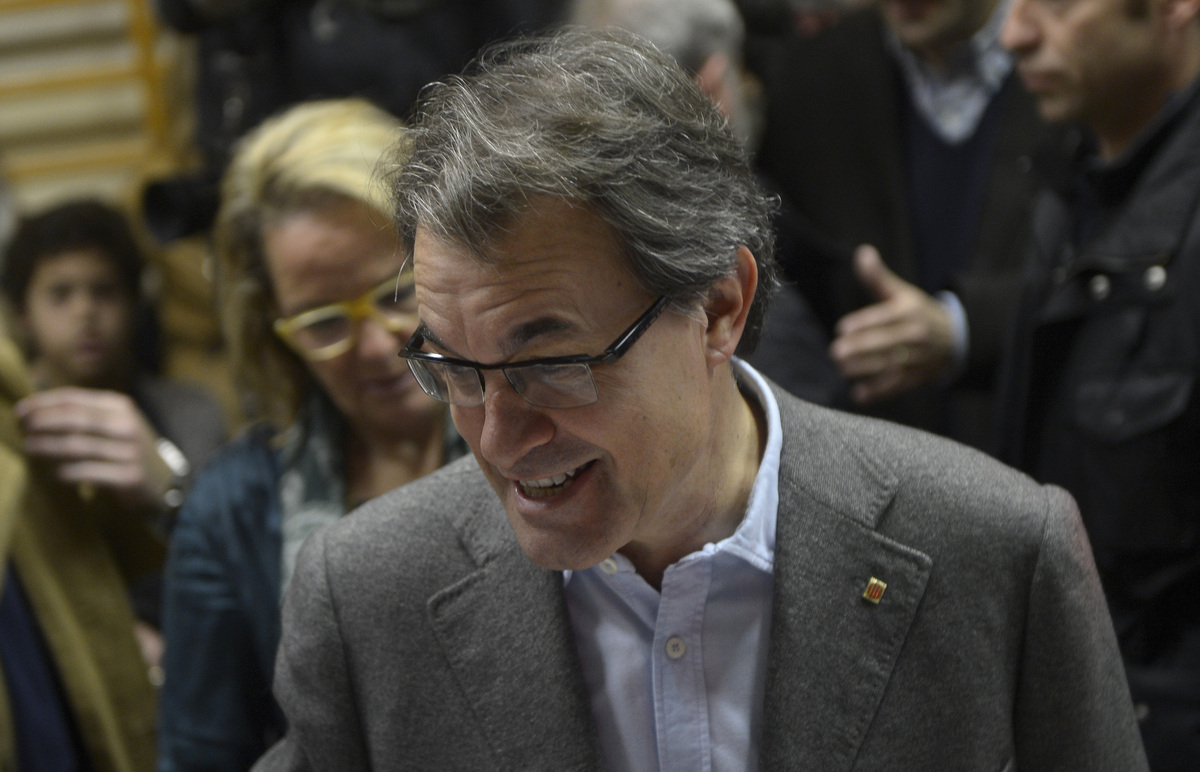 The leader of center-right Catalan Nationalist Coalition (CiU), Artur Mas smiles after casting his vote during elections for