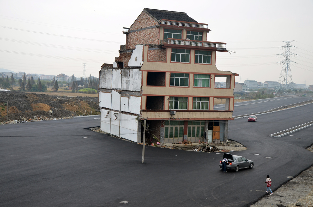 An isolated five-floor building stands in the middle of a new road on November 22, 2012 in Wenling, Zhejiang Province of Chin