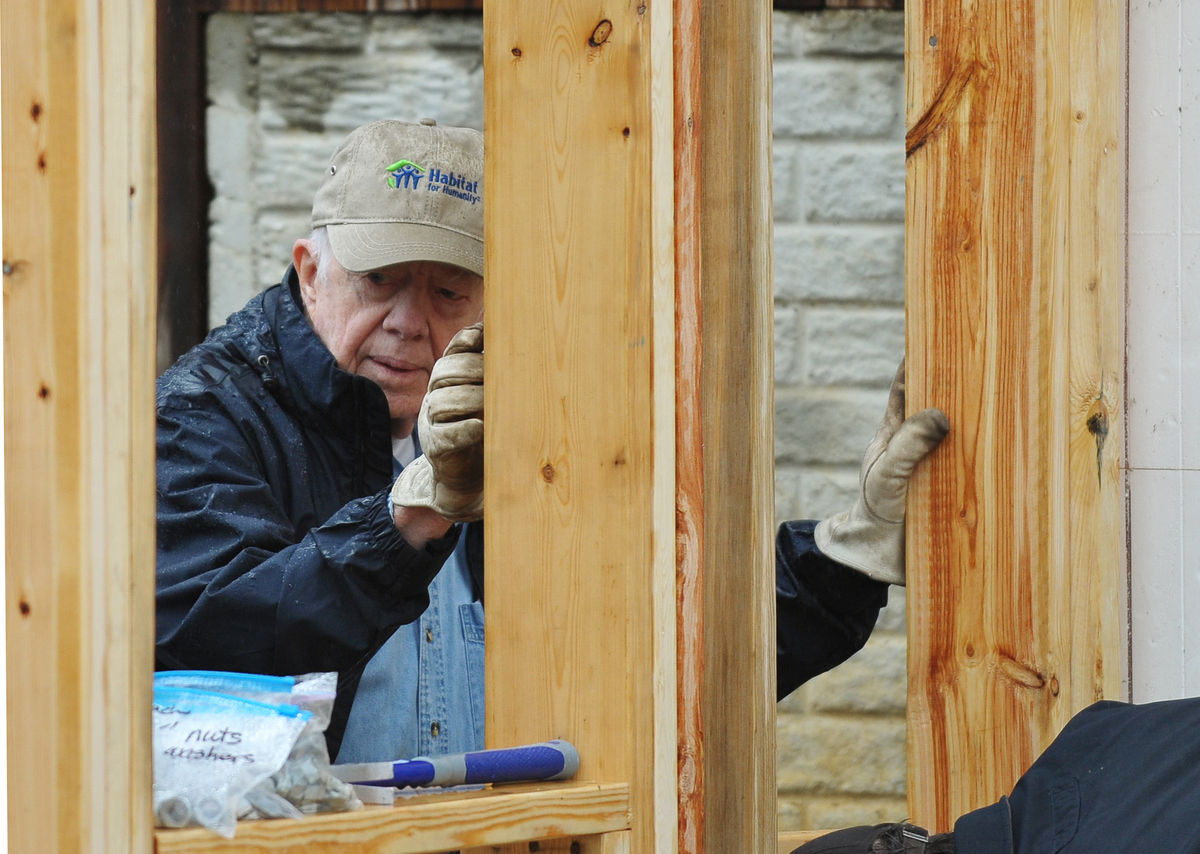 Former US president Jimmy Carter helps erect a frame during a Habitat for Humanity project October 4, 2010 in Washington, DC.