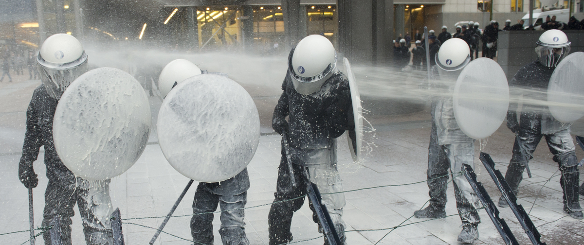 Police officers are sprayed with milk by the European milk farmers during a demonstration in front of the European Parliament