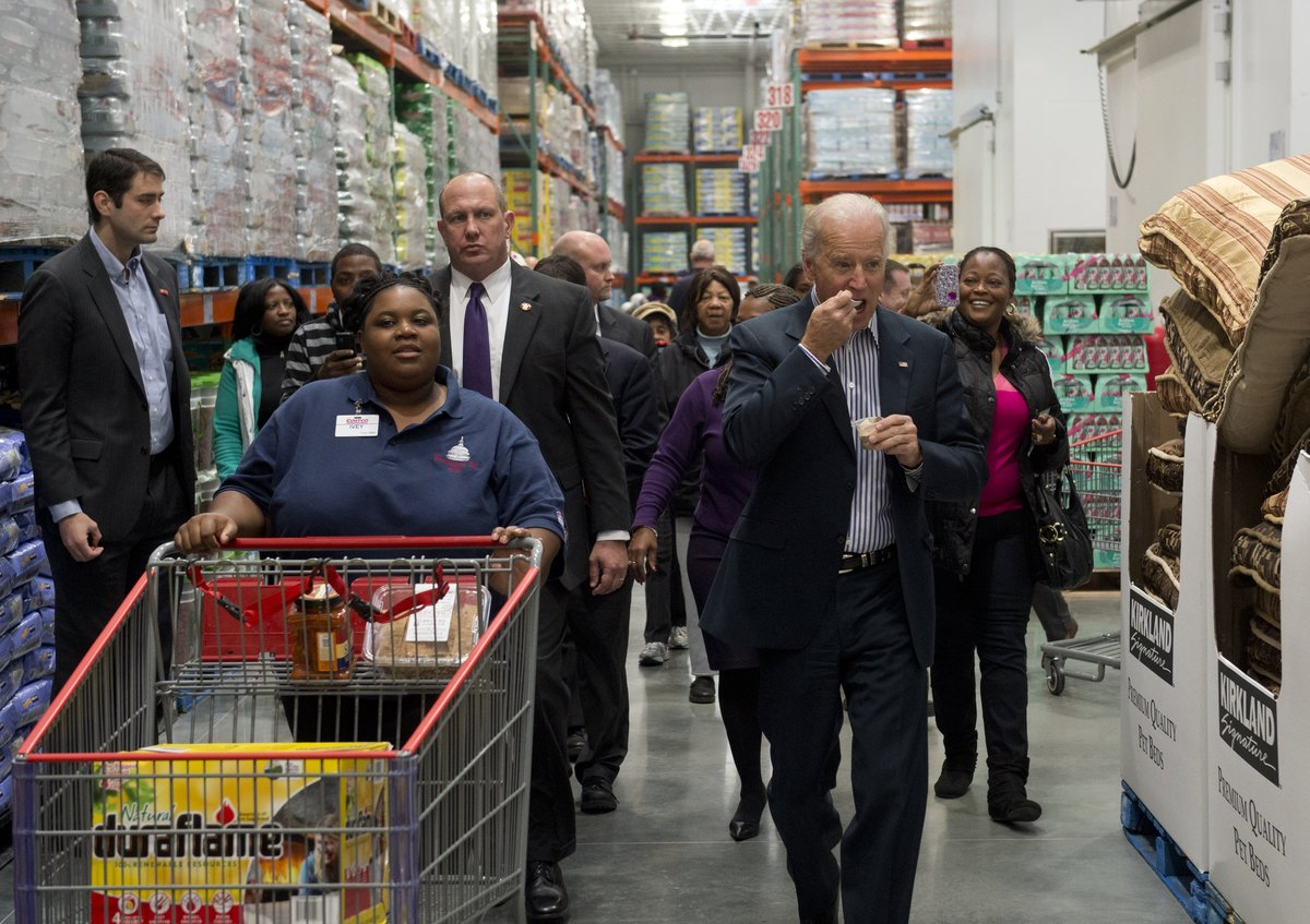 US Vice President Joe Biden eats a food sample during a visit to a Costco store on a shopping trip in Washington, DC, on Nove