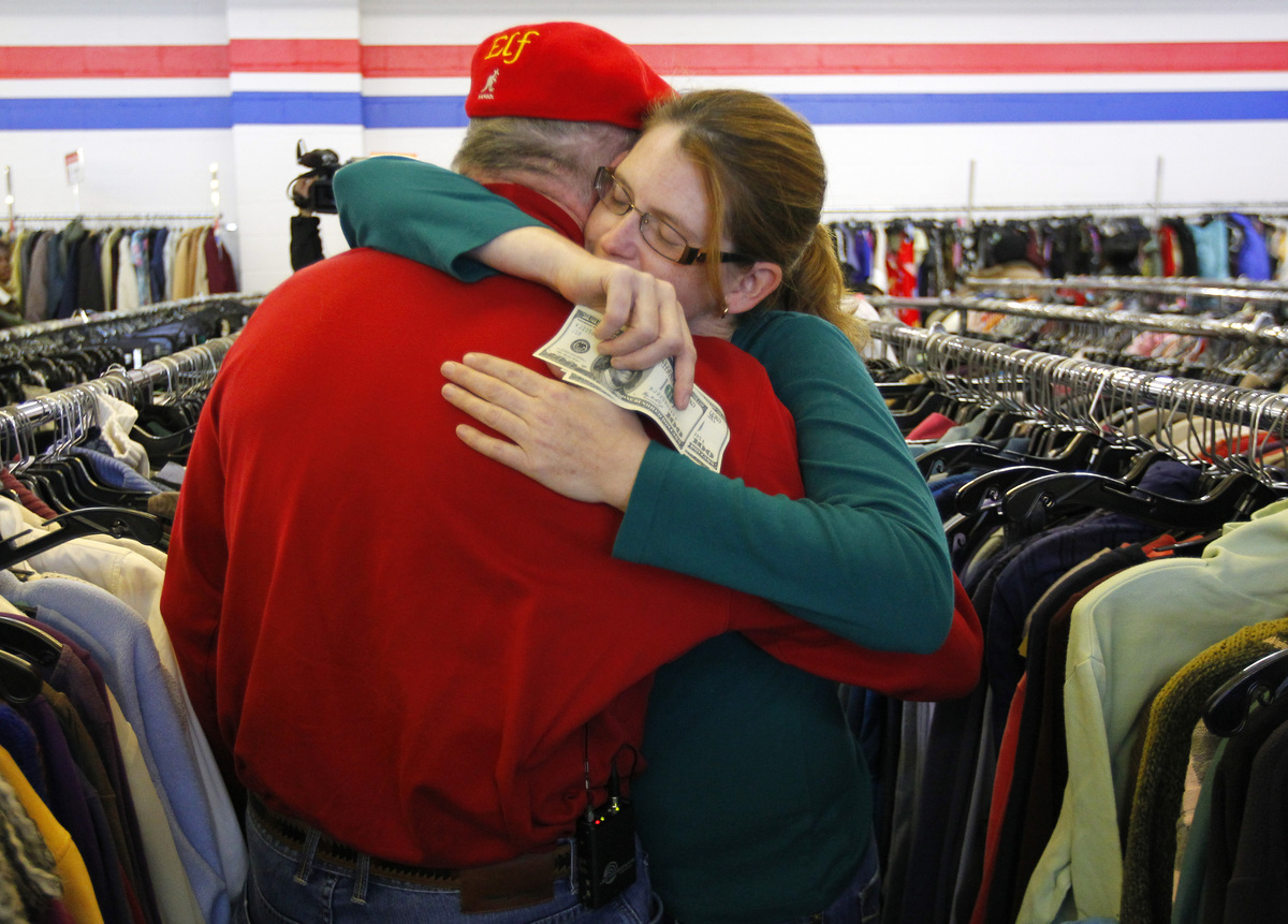 Janice Kennedy hugs Secret Santa after getting a $100 dollar bill from the wealthy philanthropist from Kansas City, Mo. while