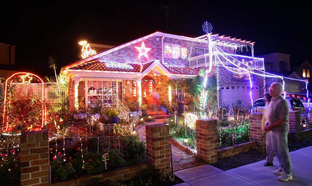 Passers-by admire a home adorned with Christmas kitsch in the Sydney suburd of Matraville on December 22, 2008. Every year cl