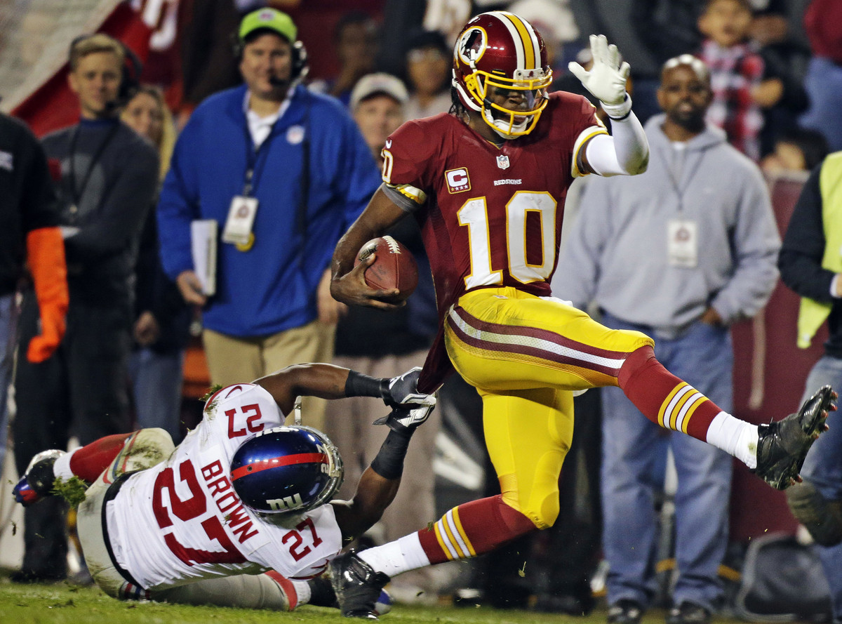 Washington Redskins quarterback Robert Griffin III (10) is pulled down by New York Giants strong safety Stevie Brown (27) dur