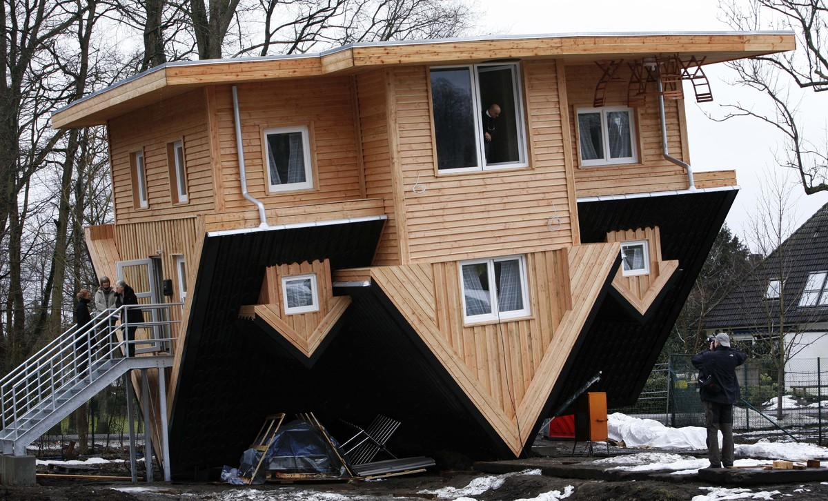 A photographer takes a picture of a wooden house which is built upside-down in Gettorf, northern Germany, on Sunday, March 14