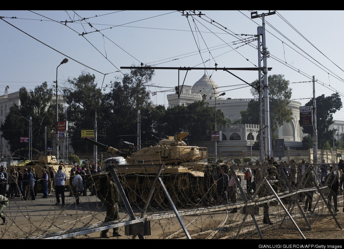 Egyptian army soldiers set up barbed wire barricades and deploy tanks outside of the Egyptian presidential palace in Cairo on