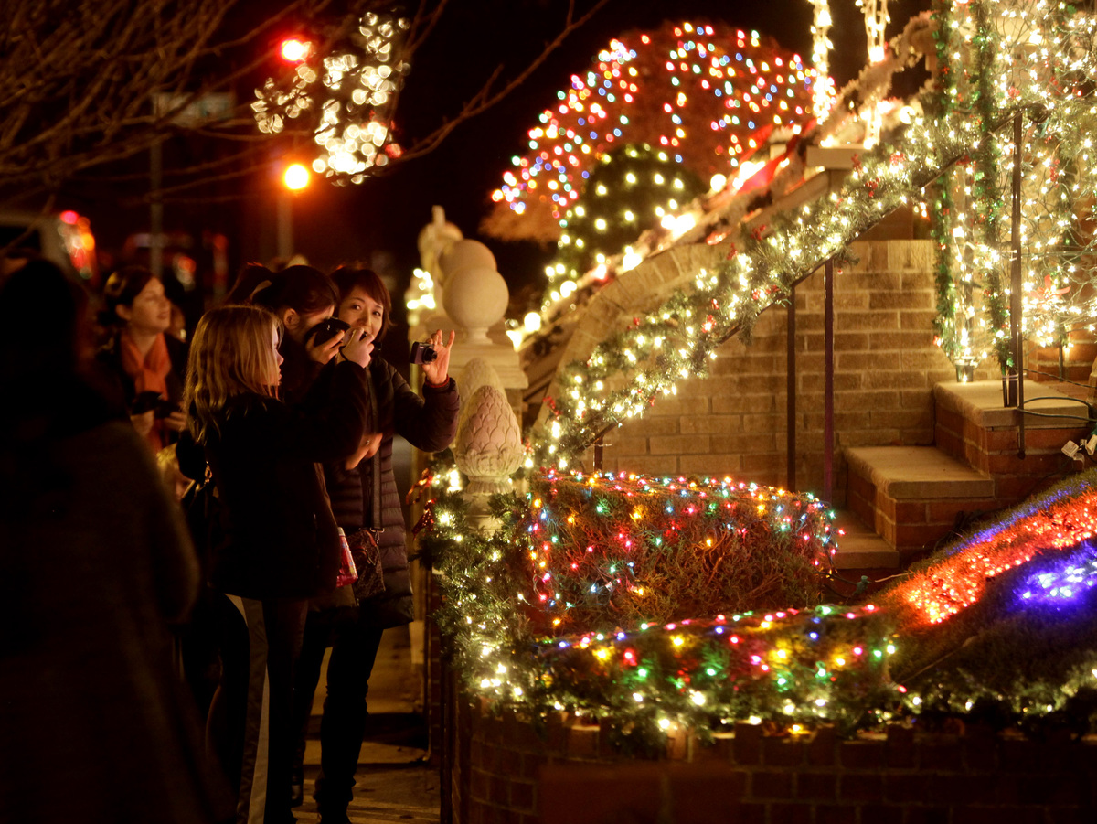 This Dec. 4, 2012 photo shows spectators viewing an elaborately decorated home for the holidays in the Brooklyn borough of Ne