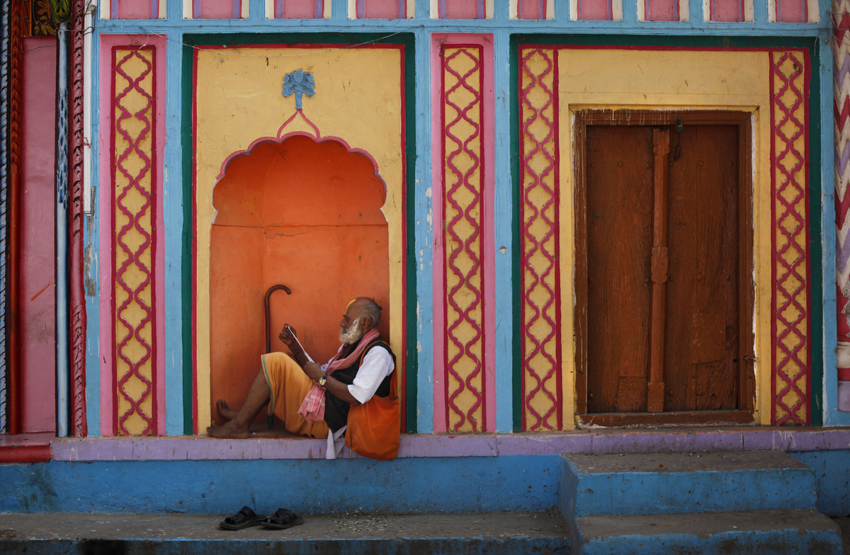 In this Thursday, Dec. 6, 2012, photo, a Hindu holy man reads a newspaper on the 20th anniversary of the Babri mosque demolit