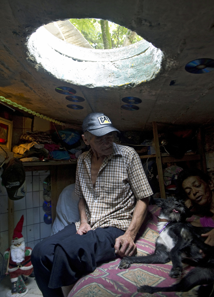 Colombian Miguel Restrepo (L), rests with his wife Maria Garcia and their dog on a bed inside a sewer on December 4, 2012, in