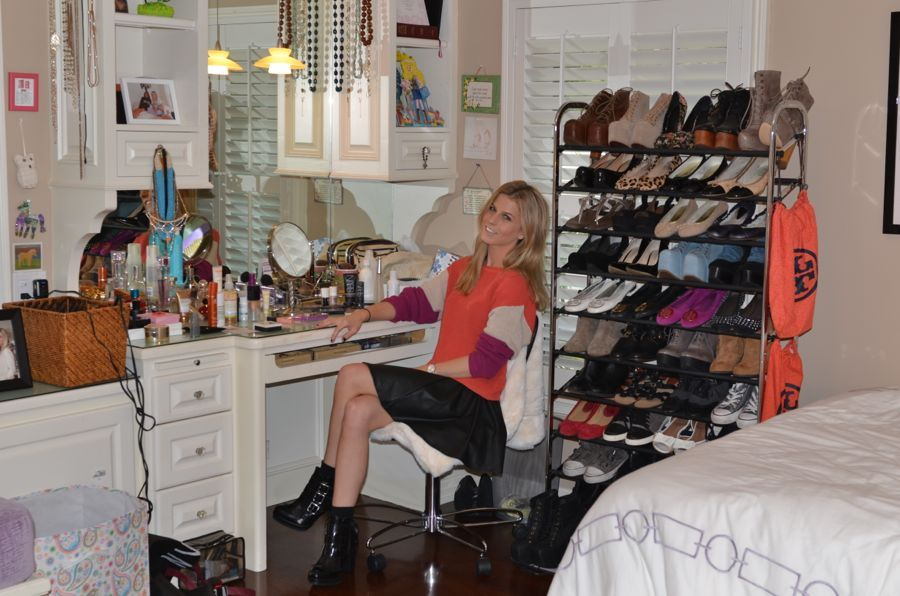 Lindsay in her bedroom where one of her extra shoe racks is parked between her bed and her vanity station.