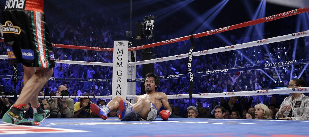 Juan Manuel Marquez, from Mexico, left, stands over Manny Pacquiao, from the Philippines, after knocking him down in the thir