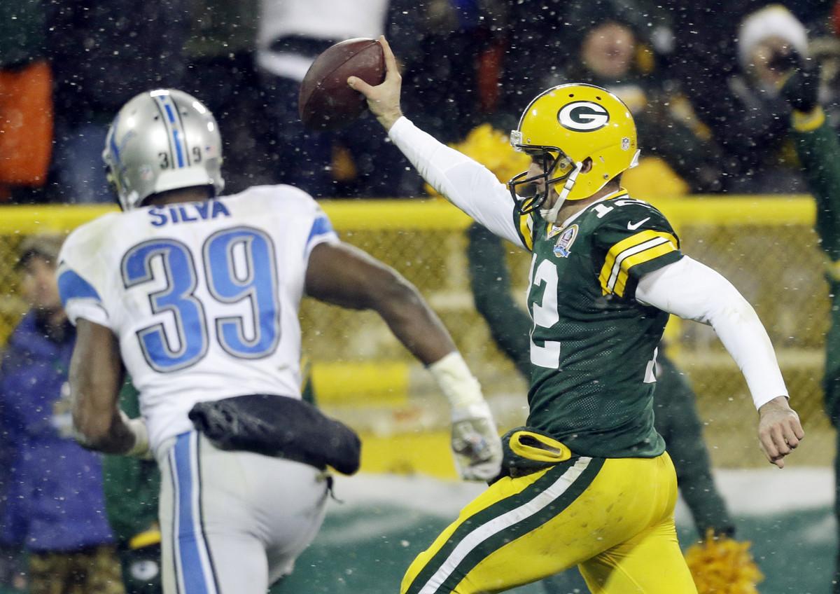 Green Bay Packers quarterback Aaron Rodgers breaks away from Detroit Lions' Ricardo Silva (39) for a 27-yard touchdown run du